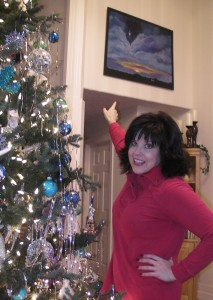 """Sarah pointing to a painting she did that became the cover of The Christmas Dreams album by Michael Allen Harrison."""